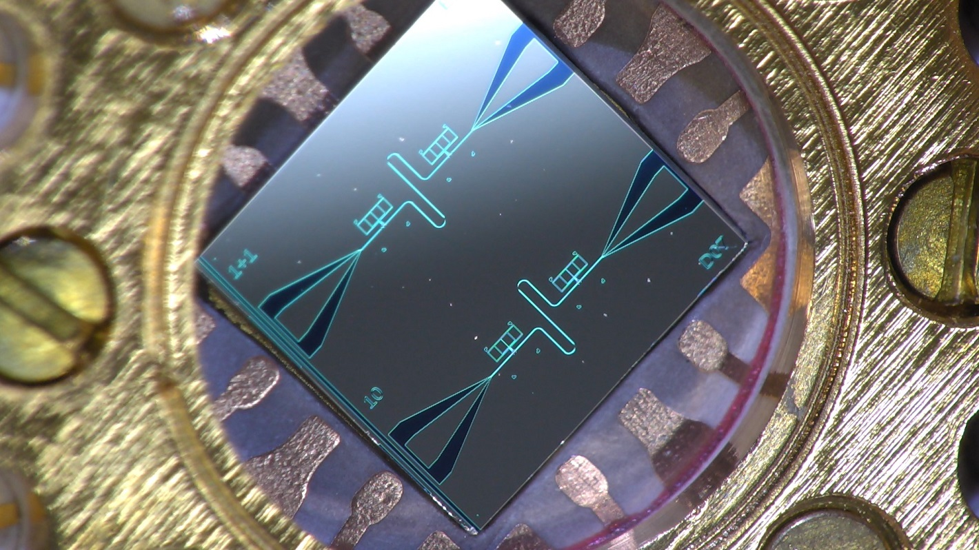 Photo of a centimeter-sized silicon chip, which has two parallel superconducting resonators and quantum-circuit refrigerators connected to them