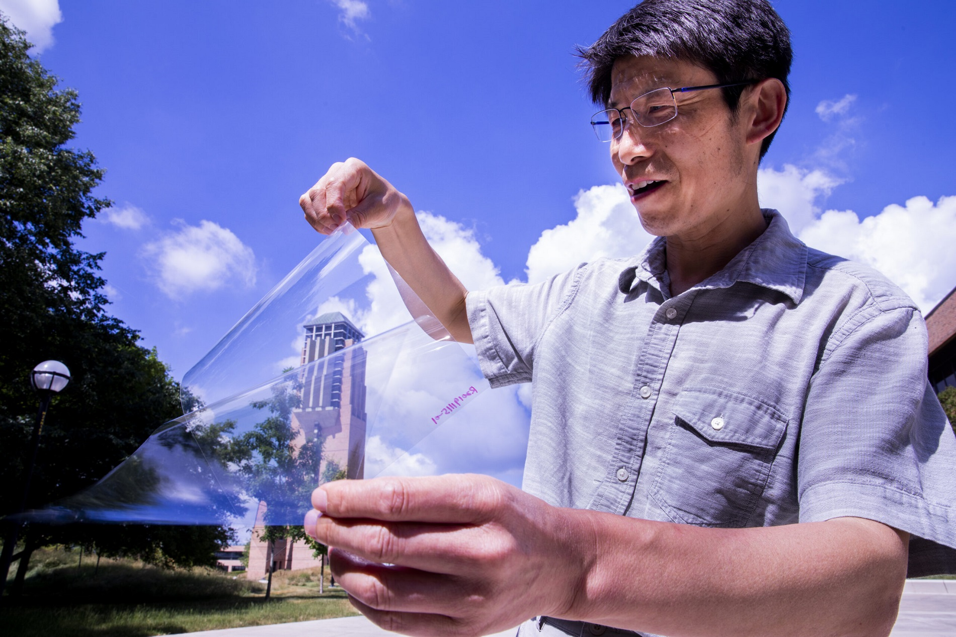 Jay Guo holds a sheet of flexible transparent conductor on the University of Michigan's College of Engineering North Campus