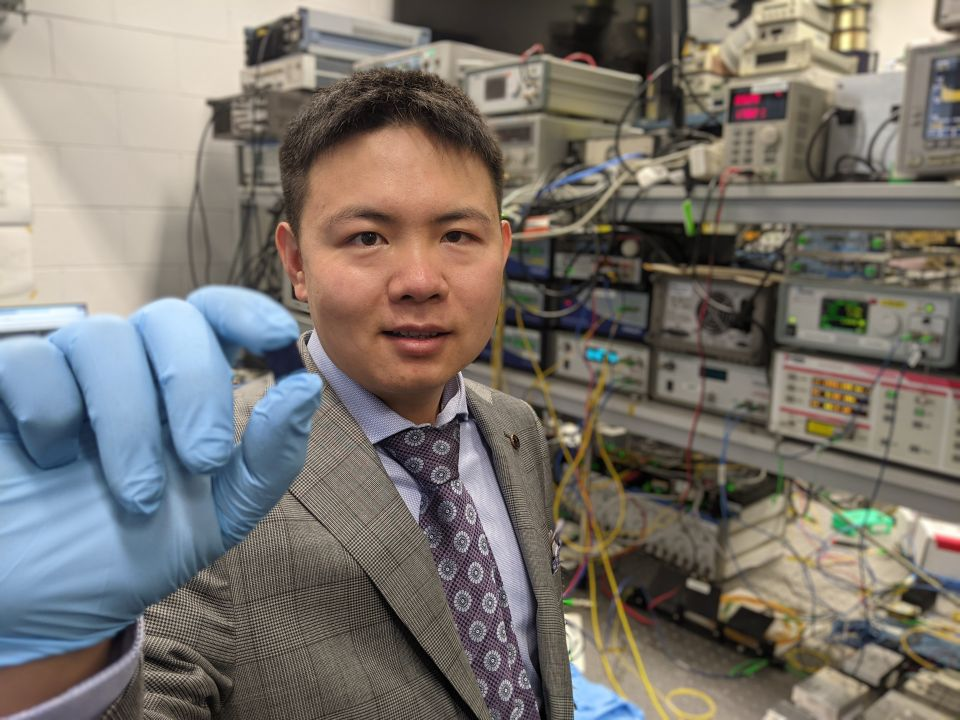 Dr Xingyuan Xu with the integrated optical microcomb chip, which forms the core part of the optical neuromorphic processor.