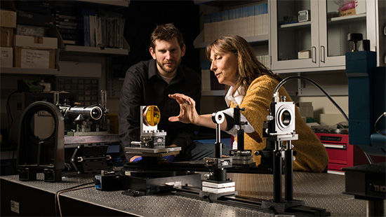 Jannick Roland works with a graduate student on a freeform lens experiment