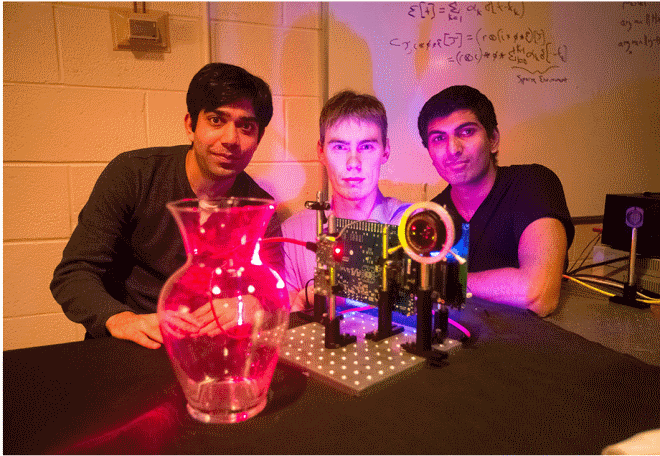"MIT students Ayush Bhandari, Refael Whyte and Achuta Kadambi pose next to their ""nano-camera"" that can capture translucent objects, such as a glass vase, in 3-D."