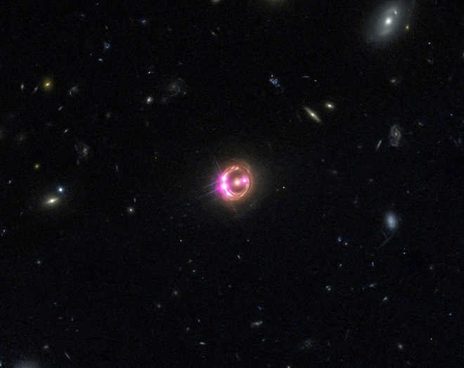 Multiple images of a distant quasar are visible in this combined view from NASA's Chandra X-ray Observatory and the Hubble Space Telescope
