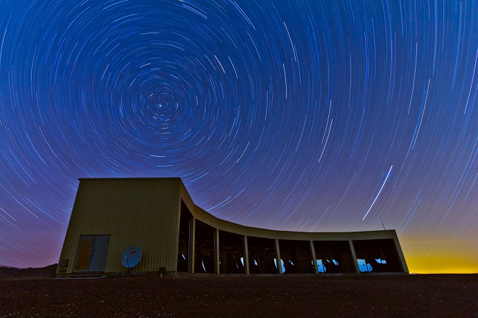n this time-lapse photo, stars appear to rotate above the Middle Drum facility of the Telescope Array