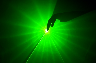 a hand in a green light lighted from a laser effect show