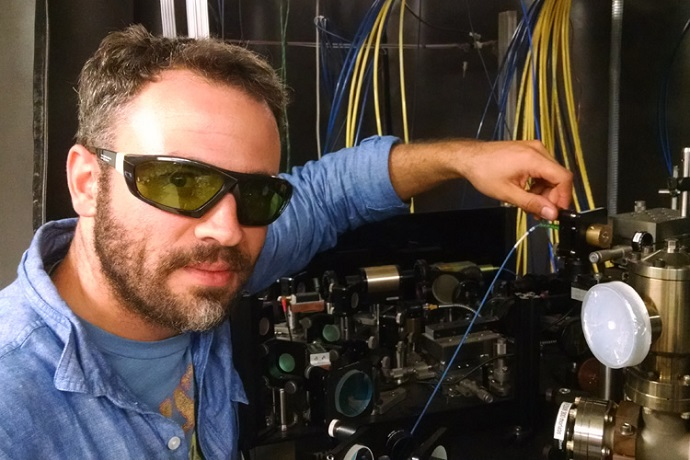 Ryan Olf dons protective glasses to adjust the lasers and vacuum chambers required to trap and cool Bose-Einstein Condensates