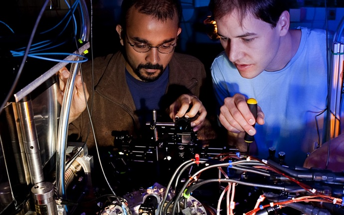 Lead author Varun Vaidya and former graduate student Creston Herold work on the apparatus