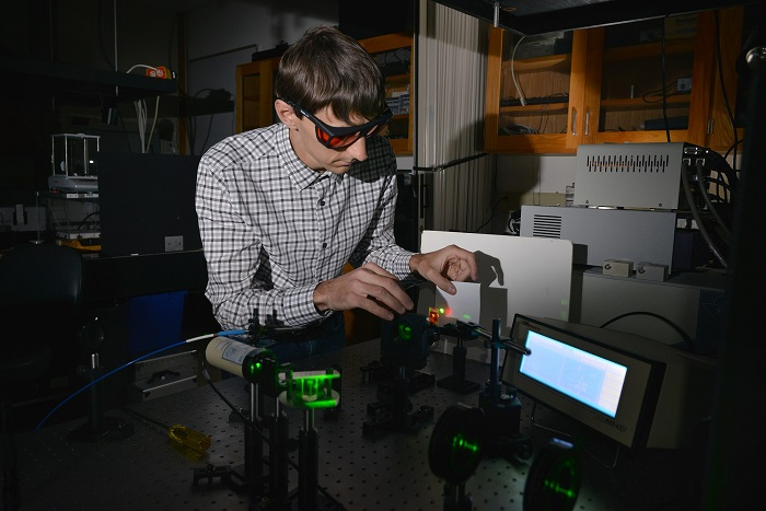 Kent State University chemical physics graduate student Andrii Varanytsia demonstrates laser emission with a liquid crystal elastomer in Professor Peter Palffy-Muhoray's lab