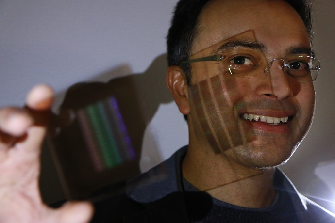 University of Utah electrical and computer engineering professor Rajesh Menon holds up the prototype of the first flat thin camera lens that he and his team developed