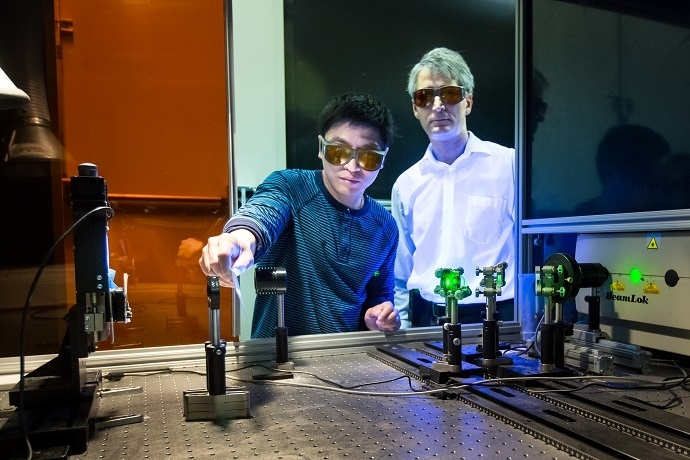 Adrian Sabau and Jian Chen work with a laser