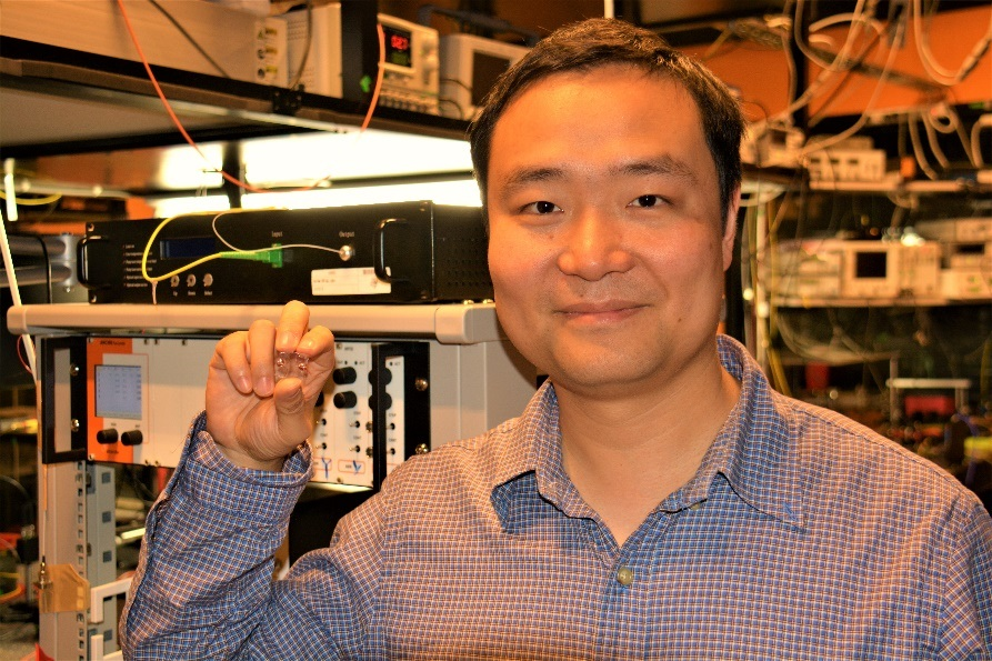 Dr. Yong Yang holding the near-invisible micro-bubble resonator mounted on a small glass microscope slide