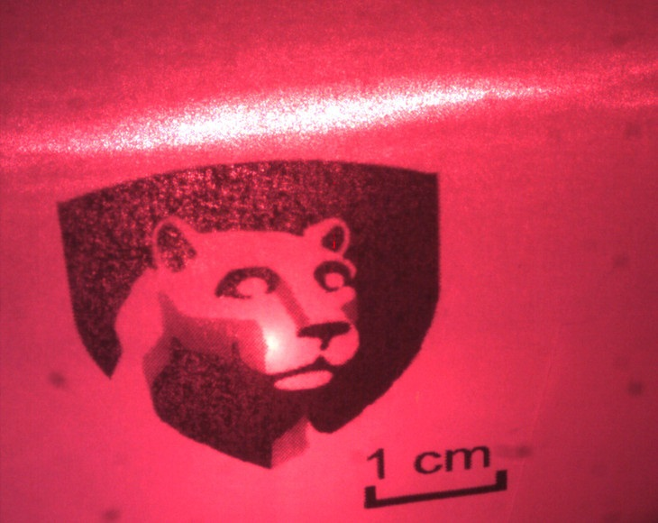 A red laser beam shines on a card bearing a replica of Penn State's academic logo