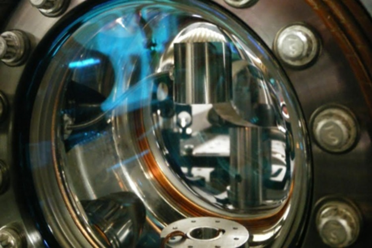 The shiny tungsten cylinder can be seen at top through a window into the vacuum chamber of the atom interferometer The cesium atoms are launched upwards through the circular opening below the cylinder
