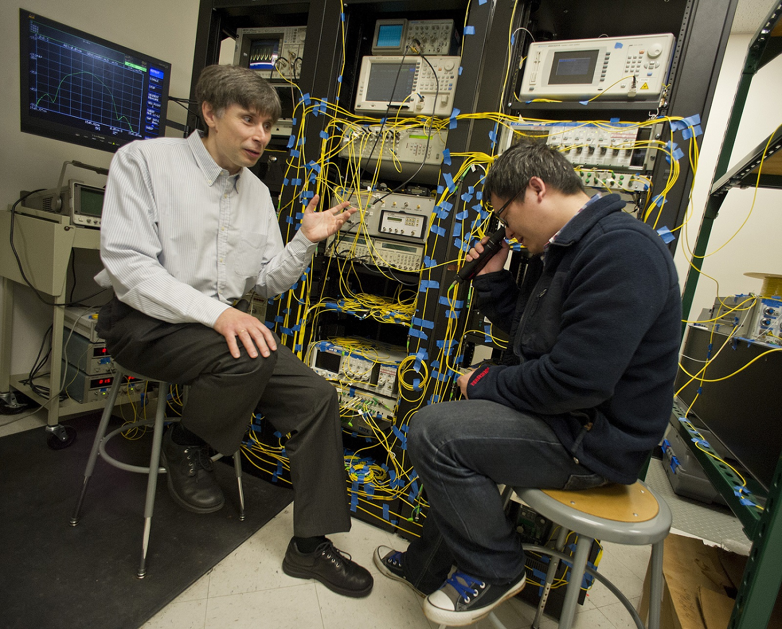 Michael Vasilyev, left, a UTA electrical engineering professor, speaks with one of his graduate students.