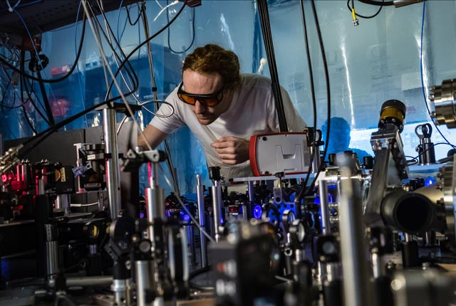 Rice University atomic physicist Joe Whalen works on a laser cooling system for ultracold strontium gas