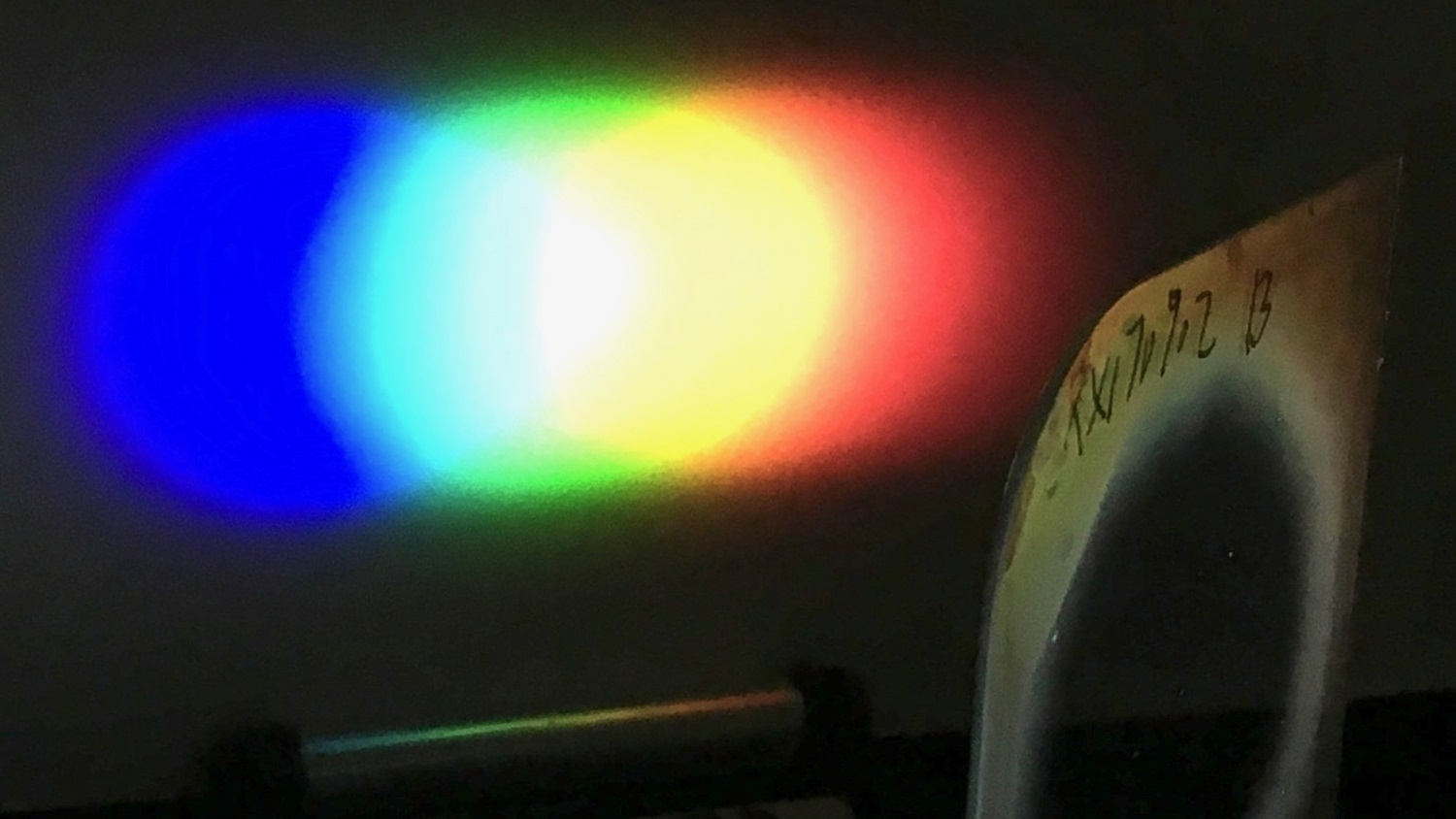 A one-inch diameter Bragg polarization grating diffracts white light from an LED flashlight onto a screen placed nearby