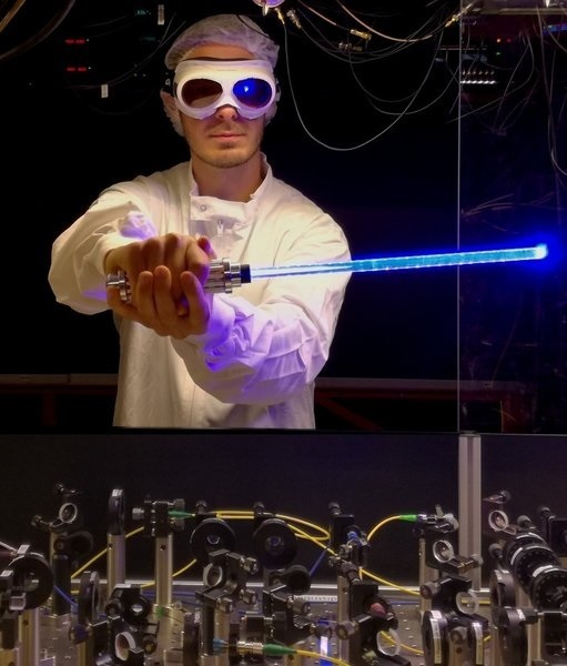 PhD candidate Nicolas Tolazzi holding a toy light saber in front of the experiment
